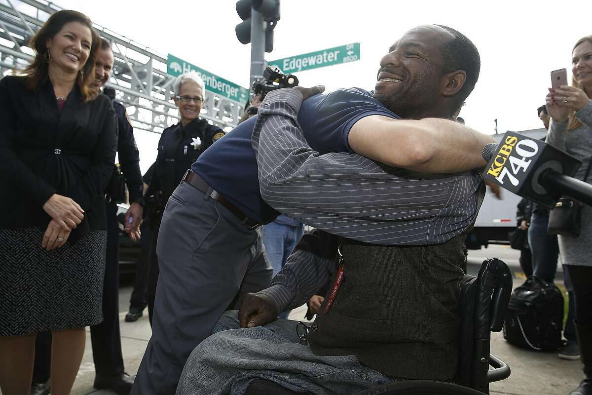 Quincey Carr gets a hug on the corner of Hegenberger and Edgewater Dr. for receiving a scholarship to get his flight instructor certification on Monday, November 7, 2016, in Oakland, Calif.