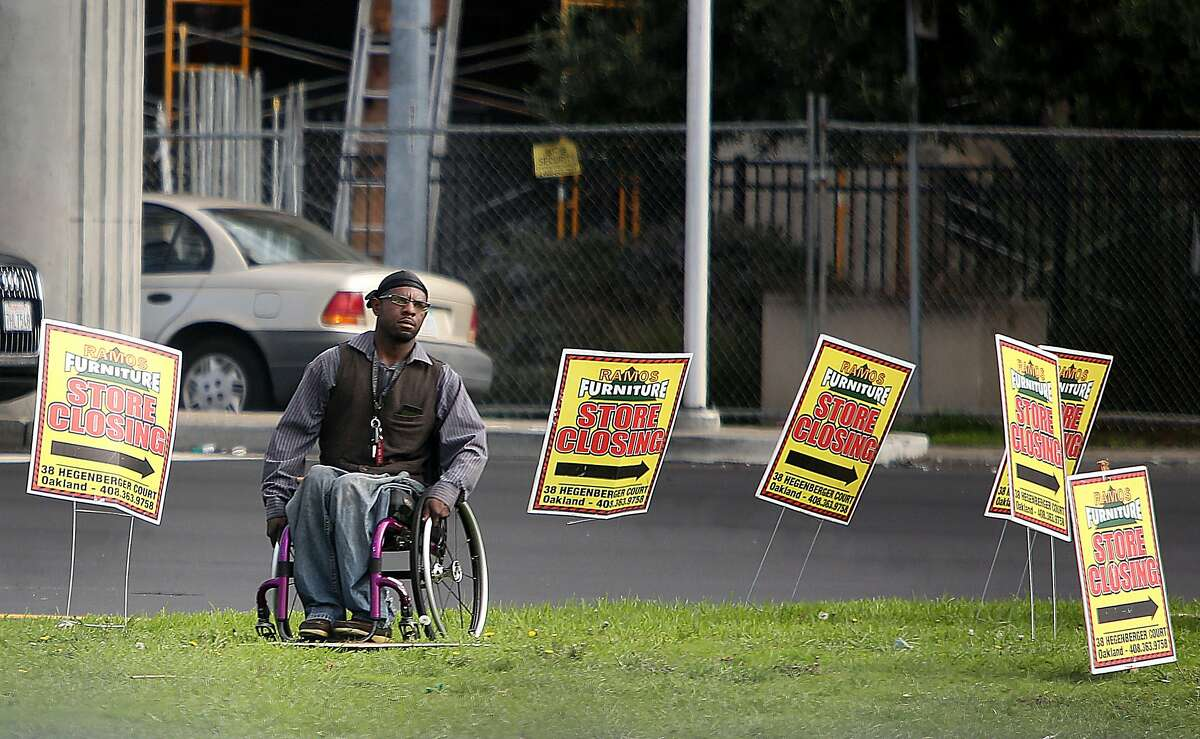 Quincy Carr uses a wheelchair since being shot by an assailant 10 years ago. He now works to attract business to a furniture store near the Oakland airport.