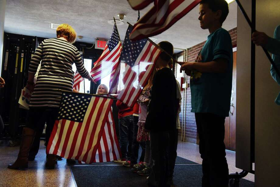 Lincoln Elementary School students who are the flag-bearers for each class line up before entering to take part in an Election Day assembly on Monday, Nov. 7, 2016, in Scotia, N.Y.  The school holds the event on the years of presidential elections.  The students also take part in voting in their classrooms during the day.  This year Hillary Clinton won with 133 votes, followed by Donald Trump with 94 votes and then Jill Stein and Gary Johnson each received six votes. (Paul Buckowski / Times Union) Photo: PAUL BUCKOWSKI / 20038706A