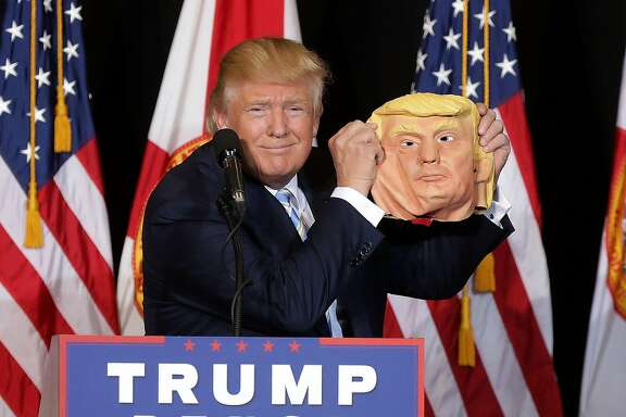 SARASOTA, FL - NOVEMBER 07:  Republican presidential nominee Donald Trump holds up a rubber mask of himself during a campaign rally in the Robarts Arena at the Sarasota Fairgrounds November 7, 2016 in Sarasota, Florida. With less than 24 hours until Election Day in the United States, Trump and his opponent, Democratic presidential nominee Hillary Clinton, are campaigning in key battleground states that each must win to take the White House.  (Photo by Chip Somodevilla/Getty Images) *** BESTPIX ***