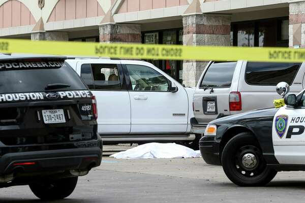 Police investigate a homicide scene where two shooting victims stopped their SUV, at a shopping center in the 5900 block of Chimney Rock Rd., Monday, Nov. 7, 2016, in Houston. The pair were shot at a Houston Can Academy campus at 9745 Bissonnet around 12:40 pm.