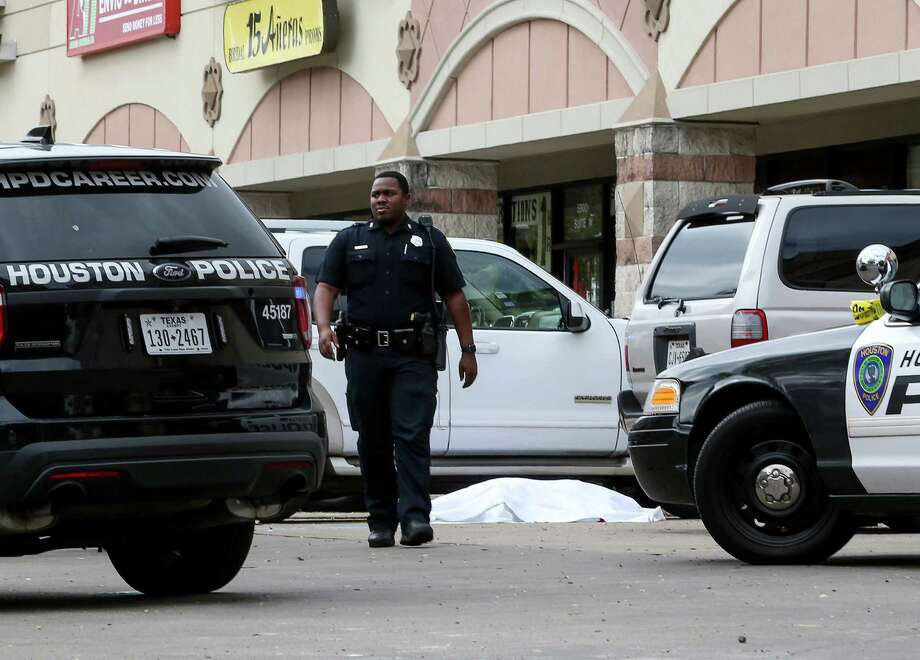 Police investigate a homicide scene where two shooting victims stopped their SUV, at a shopping center in the 5900 block of Chimney Rock Rd., Monday, Nov. 7, 2016, in Houston. The pair were shot at a Houston Can Academy campus at 9745 Bissonnet around 12:40 pm. Photo: Jon Shapley, Houston Chronicle / © 2015  Houston Chronicle