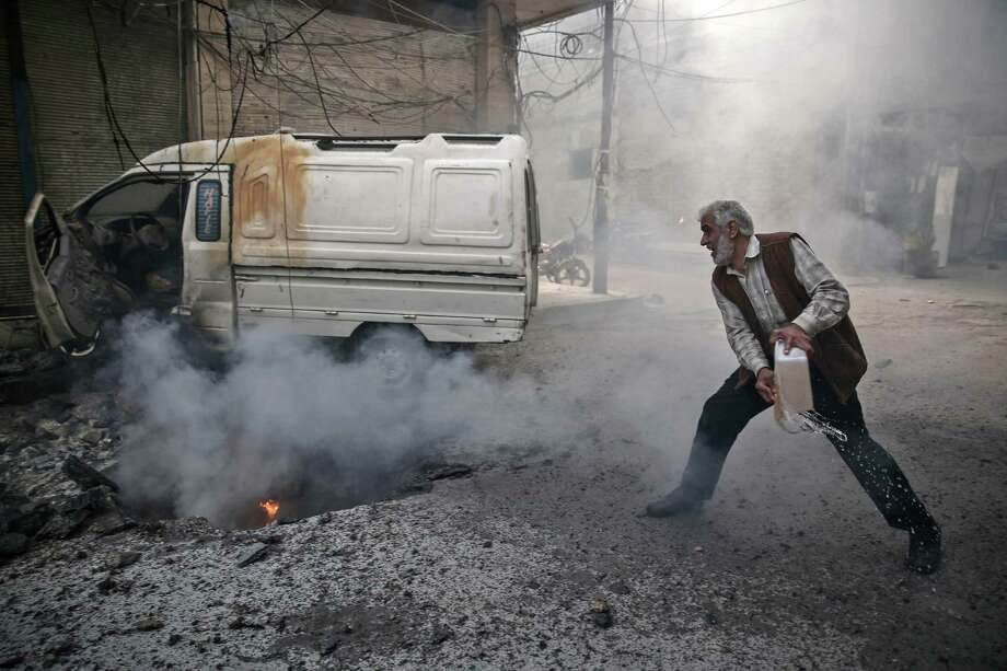 A Syrian man tries to extinguish a fire ignited by airstrikes Monday in the rebel-held town of Douma, on the eastern outskirts of Damascus. Photo: SAMEER AL-DOUMY, Stringer / AFP or licensors