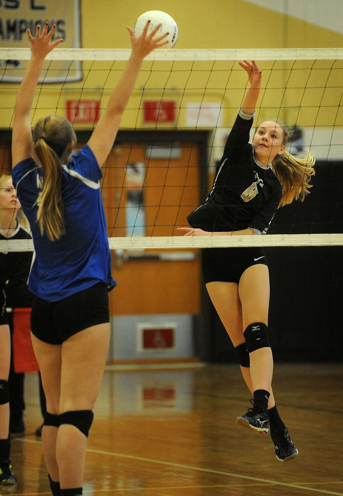 Trumbull's Katie Schels, right, spikes the ball off the Darien block on Monday.