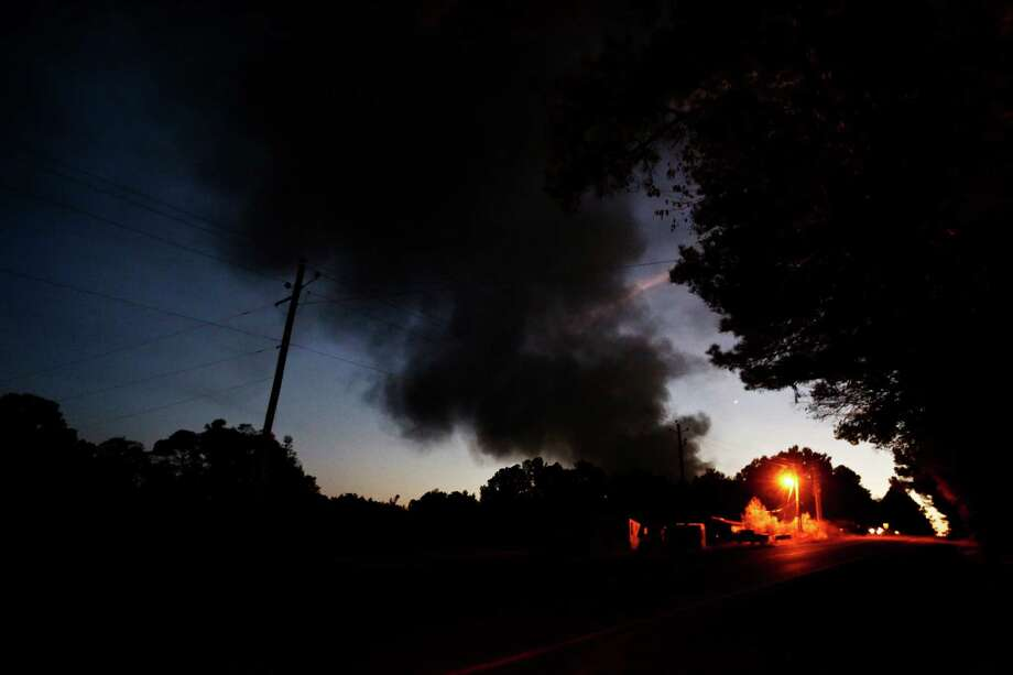 Light from a light pole shows a house near a plume of smoke from a Colonial Pipeline explosion, Monday, Oct. 31, 2016, in Helena, Ala. Colonial Pipeline said in a statement that it has shut down its main pipeline in Alabama after the explosion in a rural part of the state outside Birmingham. (AP Photo/Brynn Anderson) Photo: Brynn Anderson, STF / Copyright 2016 The Associated Press. All rights reserved.