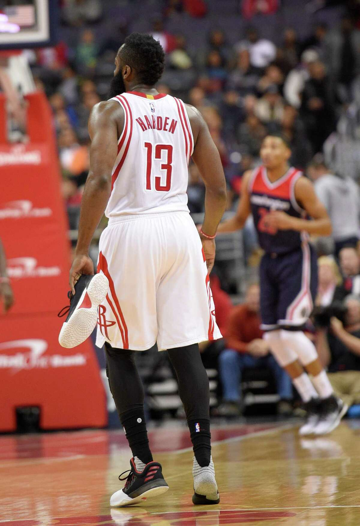 Houston Rockets guard James Harden (13) carries his shoe downcourt after it came off during the first half of an NBA preseason basketball game against the Washington Wizards, Monday, Nov. 7, 2016, in Washington. (AP Photo/Nick Wass)