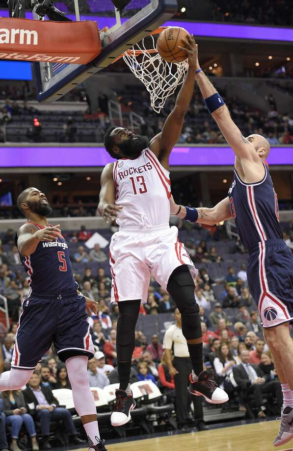 Houston's James Harden goes to the hoop against Wizards center Marcin Gortat (right) and forward Markieff Morris. Photo: Nick Wass, Associated Press