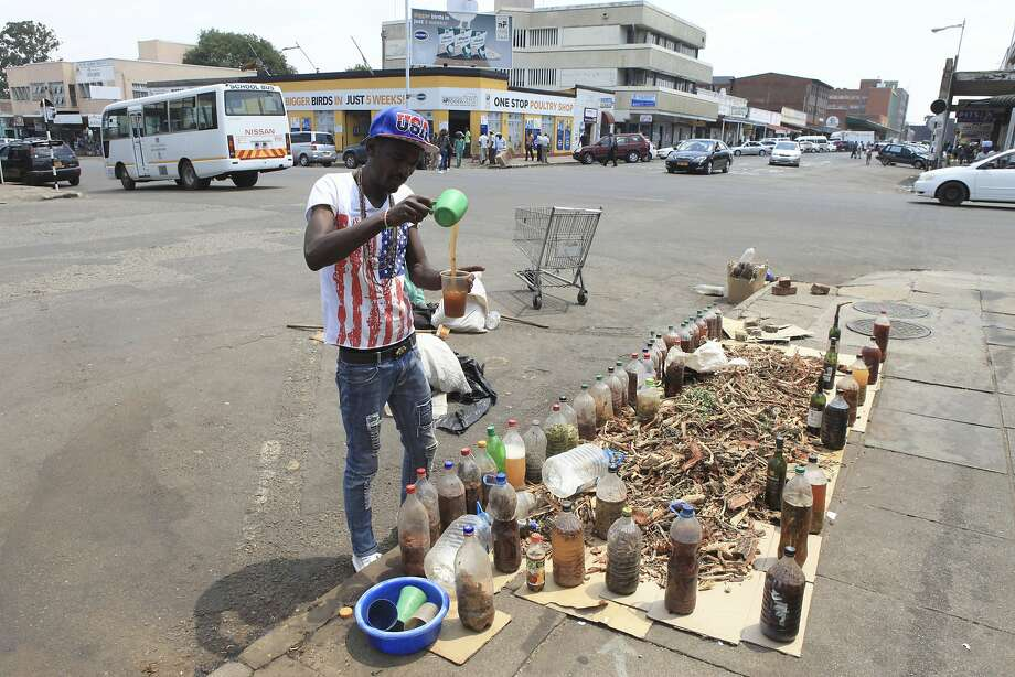 "Shepherd Mushore, a self-proclaimed ""African doctor,"" sells a variety of herbal concoctions last month on the streets of Harare, Zimbabwe. Photo: Tsvangirayi Mukwazhi, Associated Press"