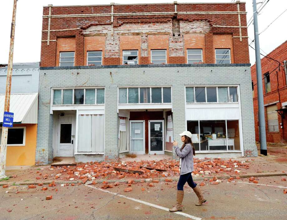 """A television reporter takes video as she walks past a damaged building in Cushing, Okla. caused by Sunday night's 5.0 magnitude earthquake, Monday, Nov. 7, 2016. Dozens of buildings sustained """"substantial damage"""" after a 5.0 magnitude earthquake struck Cushing, home to one of the world's key oil hubs, but officials said Monday that no damage has been reported at the oil terminal. (Jim Beckel The Oklahoman via AP) ORG XMIT: OKOKL201 Photo: Jim Beckel / The Oklahoman"""