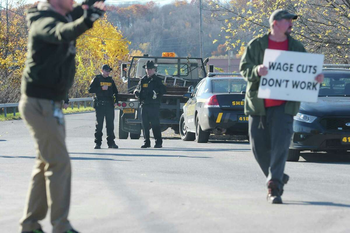 Saratoga County Sheriff's Deputies stand near a truck that was stopped after it turned onto a road near the Momentive plant where employees who are members of the UE-CWA Local 81359 union were taking part in a picket as they strike on Monday, Nov. 7, 2016, in Waterford, N.Y. The striking workers felt the driver of the truck was being reckless and endangering the workers on the picket line. A Sheriff's Deputy counseled the driver on how to drive near the striking workers, no tickets were issued. Sergeant Brent Dupras with the Saratoga County Sheriff's office said that since last Wednesday the strike began only three tickets have been issued for reckless driving and unsafe starts, and all three tickets went to the same driver he said. Sergeant Dupras said that what they have mostly been doing is counseling drivers to let them know how to operate near the striking workers. (Paul Buckowski / Times Union)