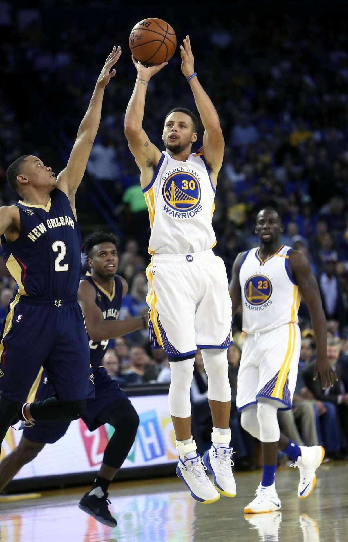 Golden State Warriors' Stephen Curry hits a 3-pointer against New Orleans Pelicans' Tim Frazier in 2nd quarter during NBA game at Oracle Arena in Oakland, Calif., on Monday, November 7, 2016.
