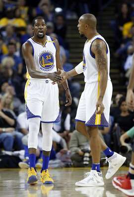 Golden State Warriors' Kevin Durant and David West slap hands after New Orleans Pelicans called a 2nd quarter time out during NBA game at Oracle Arena in Oakland, Calif., on Monday, November 7, 2016.