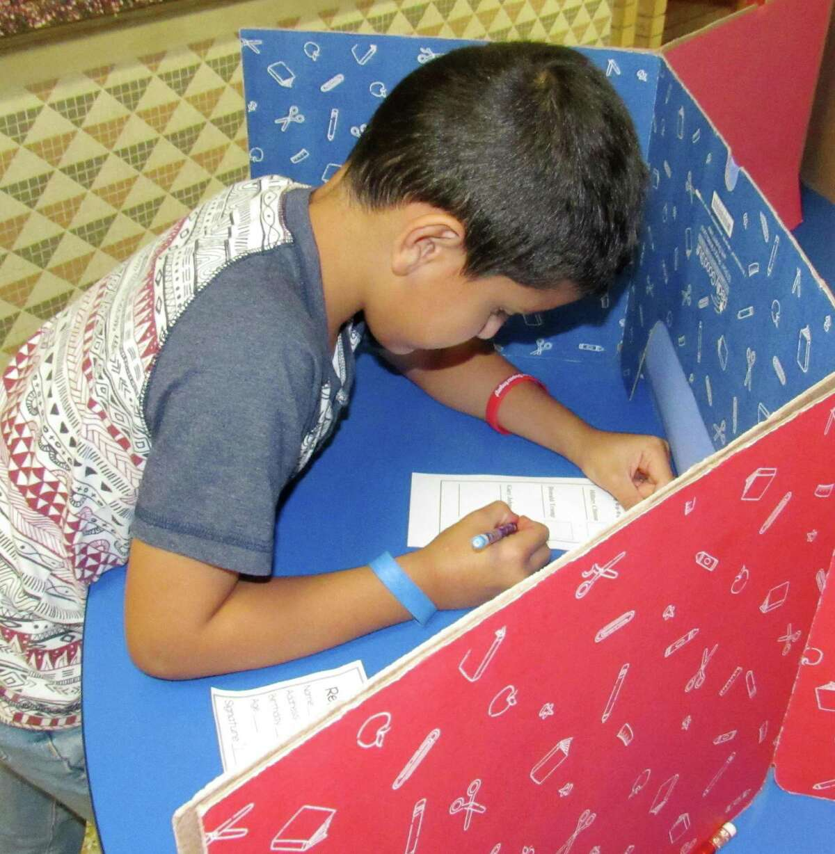 Nathan Cortez, a second-grade student at Needville Elementary, marks his ballot in a mock election Tuesday morning. Pupils presented their voter identification cards, complete with self-portraits of pencil and crayon, to polling workers (fellow students) before voting.