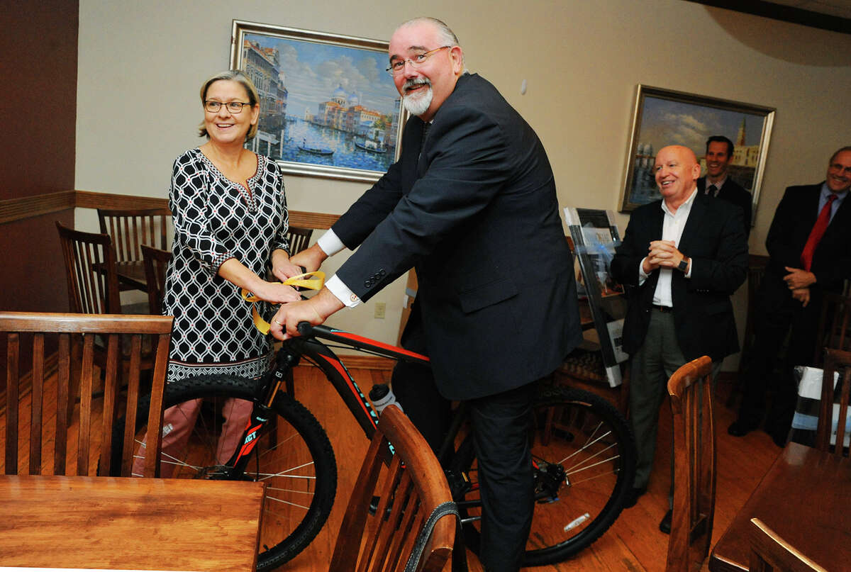 Tomball Mayor Gretchen Fagan, left, and Congressman Kevin Brady, R-The Woodlands, gave Commissioner Jack Cagle, a bicycle after they all received awards from Memorial Hermann The Woodlands officials for helping to route the cycling portion of the 2016 Ironman Texas race through Tomball.