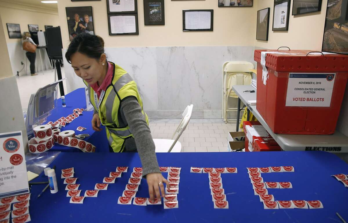Poll worker Marie Paul Serviano replaces voter stickers on Election Day at City Hall in San Francisco, Calif. on Tuesday, Nov. 8, 2016.