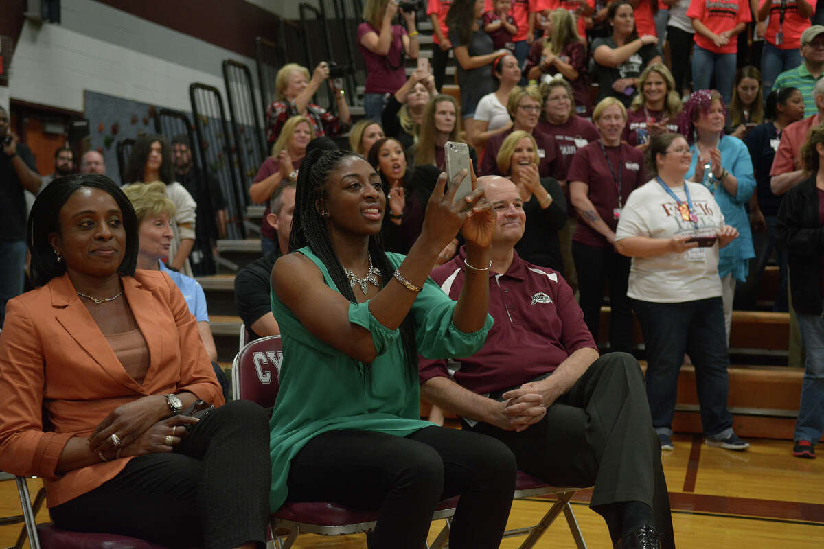 Nneka Ogwumike, center, sitting with her mom, Ify, left, and Cy-Fair ISD Superintendent Mark Henry, records the cheers from Cy-Fair High School fans after her entrance into the school gym for the pep rally held in her honor on Friday, Oct. 28, 2016. (Photo by Jerry Baker/Freelance)