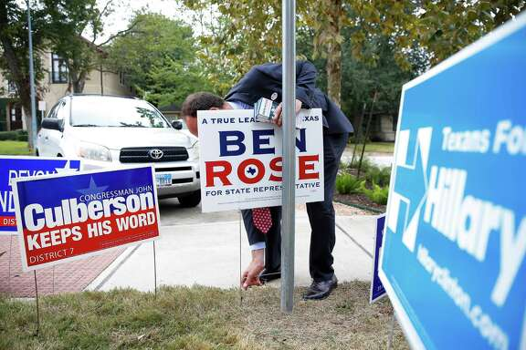 Democratic candidate for Texas House District 134 Ben Rose places a campaign sign outside of Horn Elementary School Tuesday, Nov. 8, 2016 in Houston.