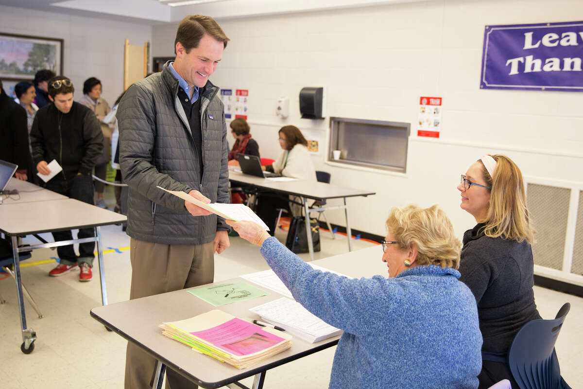 Congressman Jim Himes, D-Conn. recieves his ballot before voting at Central Middle School in Greenwich, Conn. on Tuesday morning, Nov. 8, 2016.