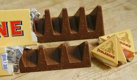 In this photo illustration two bars of the Toblerone Swiss chocolate are shown, at front is the new style 150 gram bar showing the reduction in triangular pieces, in the background is the older style 360 gram bar, pictured in London, Tuesday, Nov. 8, 2016. More valleys, fewer chocolate peaks: The maker of Toblerone Swiss chocolate says it's widened the spaces in its iconic, triangle-array bars for some discount shops in Britain to keep prices down. Mondelez International says the move aims to meet pricing targets by customer Poundland and other discount retailers, and has nothing to do with Britain's vote to leave the European Union. (AP Photo/Alastair Grant)