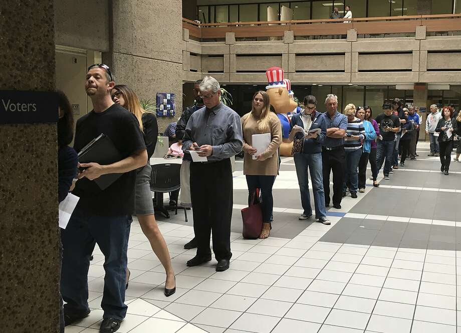 The line of voters waiting to cast an early ballot at the Santa Clara County Registrar of Voters' office winds into the building's atrium Monday in San Jose. The building was briefly evacuated Tuesday due to a slice of burned toast setting off a smoke alarm. Photo: Ramman Kenoun, Associated Press