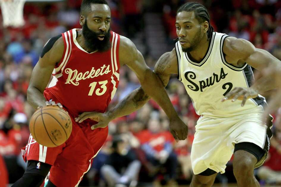 Rockets guard James Harden (13) is guarded by Spurs forward Kawhi Leonard in the first half at the Toyota Center on Dec. 25, 2015, in Houston.