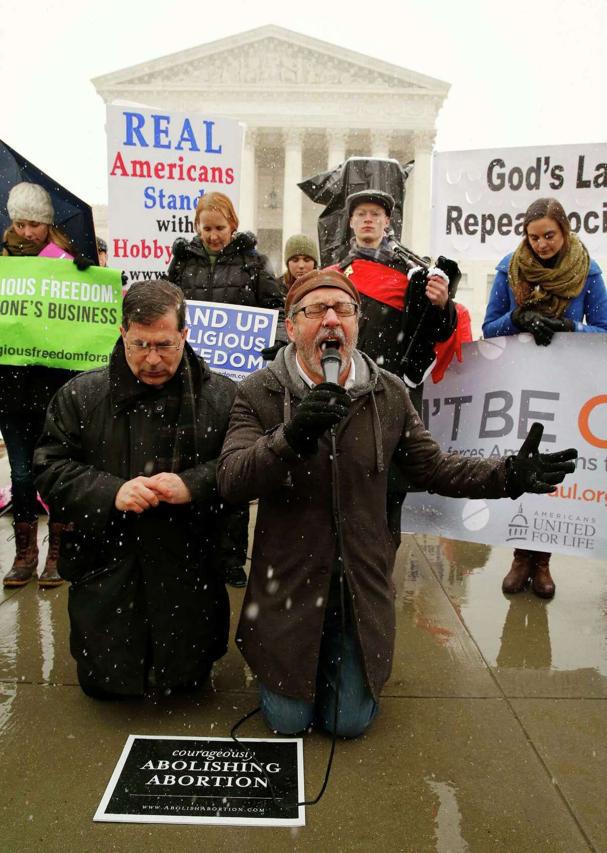 Protesters Father Frank Pavone, left, and Rev. Patrick Mahoney pray at the steps of the U.S. Supreme Court as arguments begin to challenge the Affordable Care Act's requirement that employers provide coverage for contraception as part of an employee's health care, in Washington, March 25, 2014. Click through the next photos to see elements of the history of abortion in Texas,