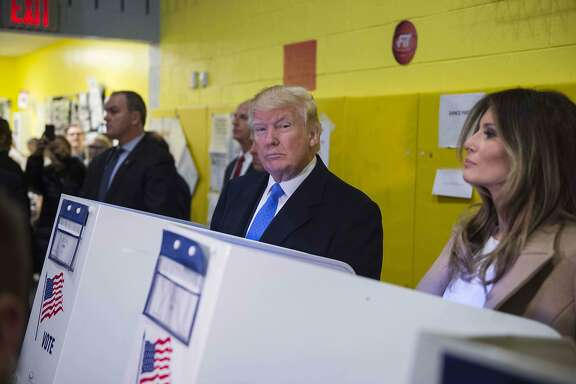 TOPSHOT - Republican presidential nominee Donald Trump(2nd R) and his wife Melania fill out their ballots at a polling station in a school during the 2016 presidential elections on November 8, 2016 in New York. / AFP PHOTO / MANDEL NGANMANDEL NGAN/AFP/Getty Images
