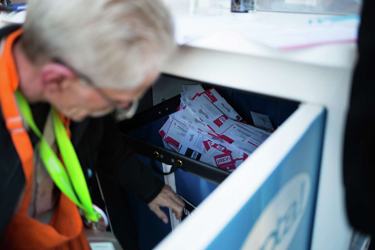 Mark Briggs collects ballots to be counted from a drop box outside Schmitz Hall at University of Washington, Tuesday, Nov. 8, 2016.