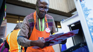 Omollo Gaya collects ballots from a dropbox outside Schmitz Hall to bring to a counting facility, at University of Washington, Tuesday, Nov. 8, 2016.