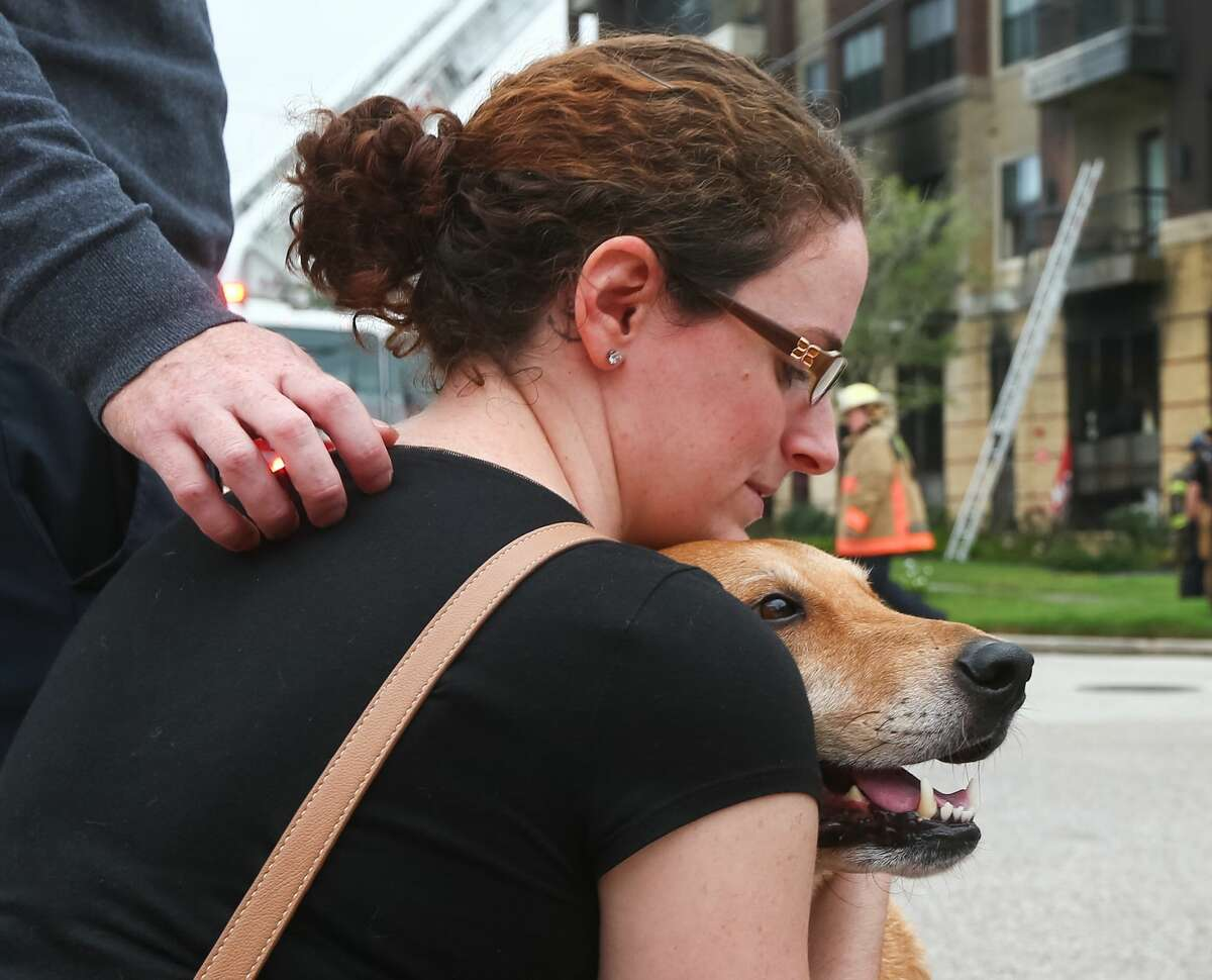 Valerie McGill hugs her dog after firefighters found it hiding in her fourth-floor apartment, Tuesday, Nov. 8, 2016, in Houston. Firefighters responded to a two-alarm fire at the intersection of La Branch Street and Blodgett Street