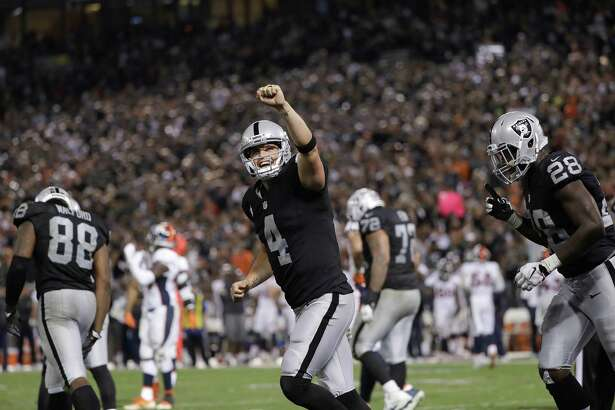 FILE - In this Nov. 6, 2016, file photo, Oakland Raiders quarterback Derek Carr (4) celebrates after a touchdown run by Latavius Murray during the second half of an NFL football game against the Denver Broncos in Oakland, Calif. The Raiders are seeking their first playoff berth since 2002. (AP Photo/Marcio Jose Sanchez, File)