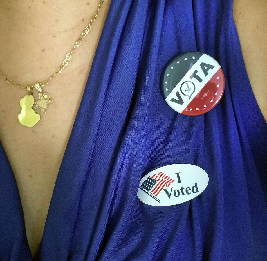 "Rosa Gutierrez, 50, of Danbury, a native of Puerto Rico, wears her ""I Voted"" stickers - in both English and Spanish, Tuesday, Nov. 8, 2016. Photo: Carol Kaliff / Hearst Connecticut Media / The News-Times"