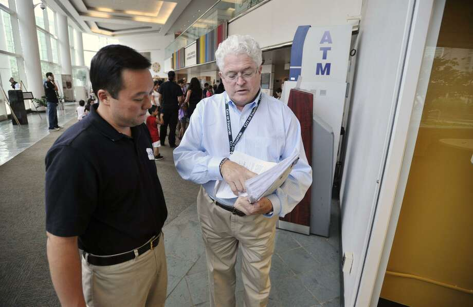Stamford's Democratic registrar of Voters, Ron Malloy, talks with state Rep. William Tong during a 2013 visit by Tong to Stamford Government Center. Photo: File Photo / Stamford Advocate