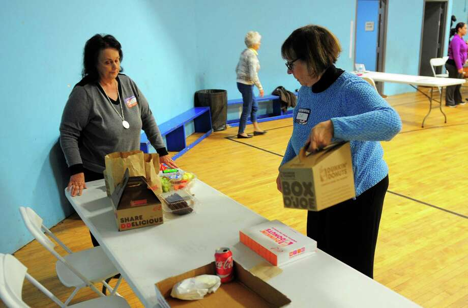 Assistant Registrar of Voters Anita Bazelewicz, left, and poll worker Sue Horelick put out coffee and doughnuts inside the gym of the old Ansonia Armory in Ansonia, Conn., on Tuesday Nov. 8, 2016. Photo: Christian Abraham, Hearst Connecticut Media / Connecticut Post