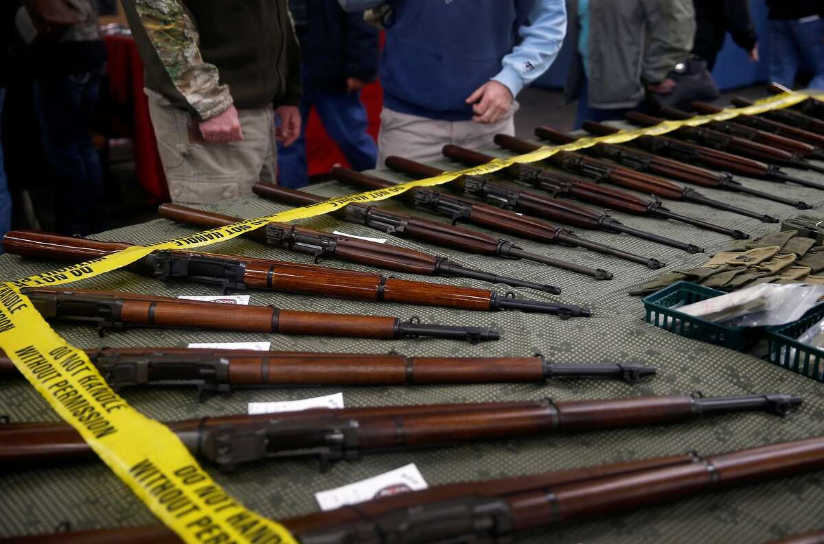 A vendor displays a collection of rifles at the Crossroads of the West gun show at the Cow Palace in Daly City, Calif. on Saturday, Jan. 9, 2016.
