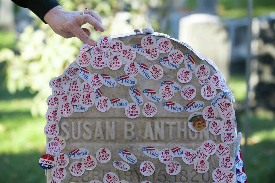 A woman adds to the voting stickers on the headstone of Susan B. Anthony, a women's suffrage pioneer, on Election Day in Rochester, N.Y. Photo: KATHERINE TAYLOR, STR / NYTNS