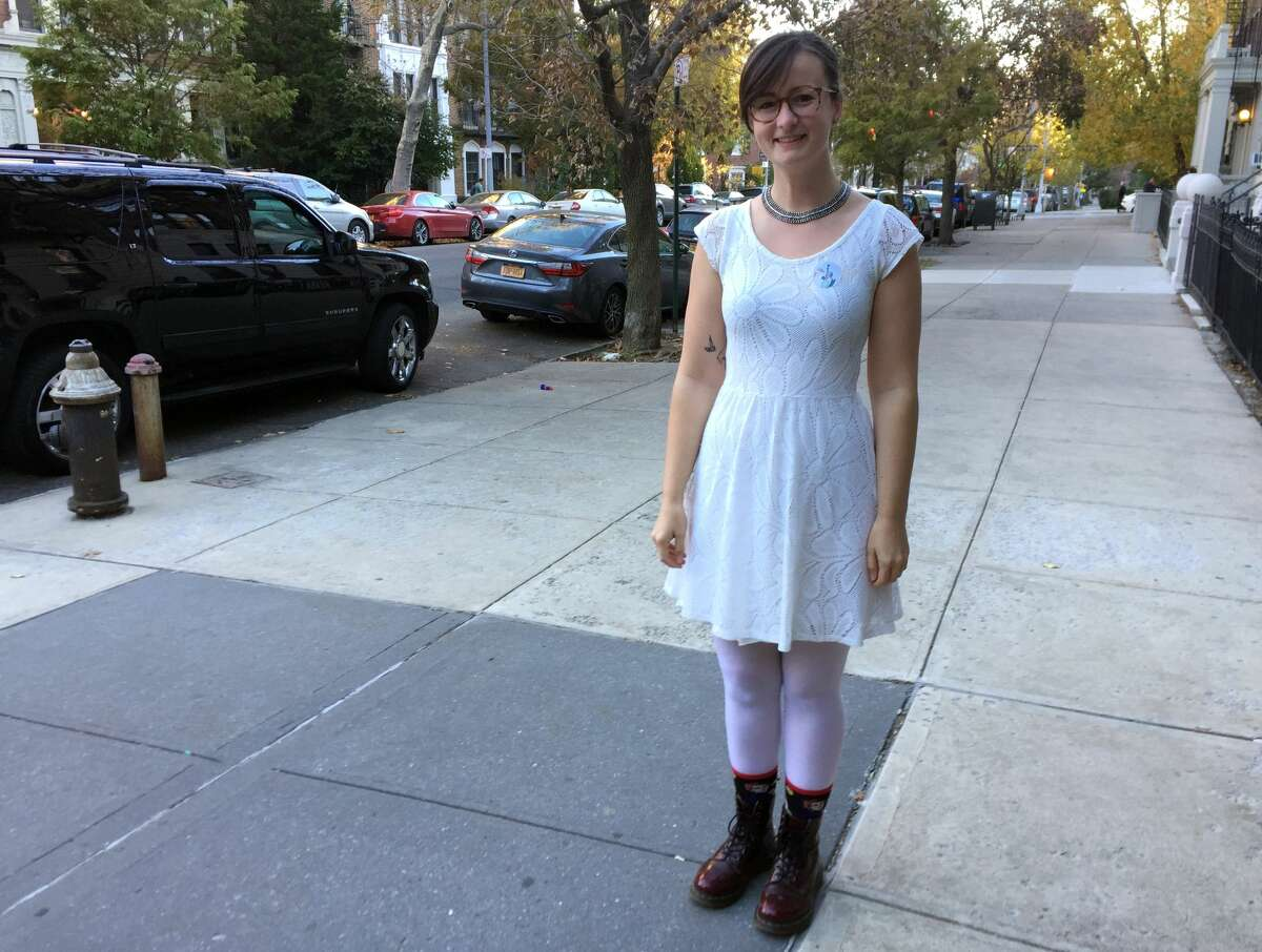 Lucy Bonner of Brooklyn, N.Y., poses Tuesday, Nov. 8, 2016, dressed in white after voting for Hillary Clinton. Some Clinton supporters wore the color white in honor of the suffragettes, who wore white when they fought for women's right to vote in the early 1900s.