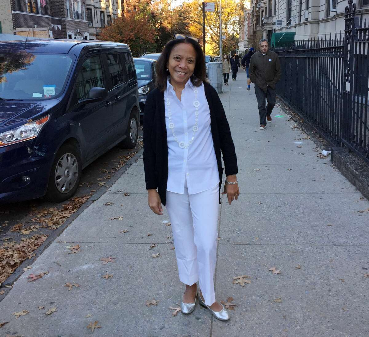 Sophia Romero of Brooklyn, N.Y., poses dressed in white Tuesday, Nov. 8, 2016, near her polling place after voting for Hillary Clinton. Some of Clinton's supporters dressed in white as a tribute to the suffragists, who wore white in their fight to get women the right to vote in the early 1900s. Others wore pantsuits in a nod to Clinton's typical campaign uniform. (AP Photo/Beth J. Harpaz)