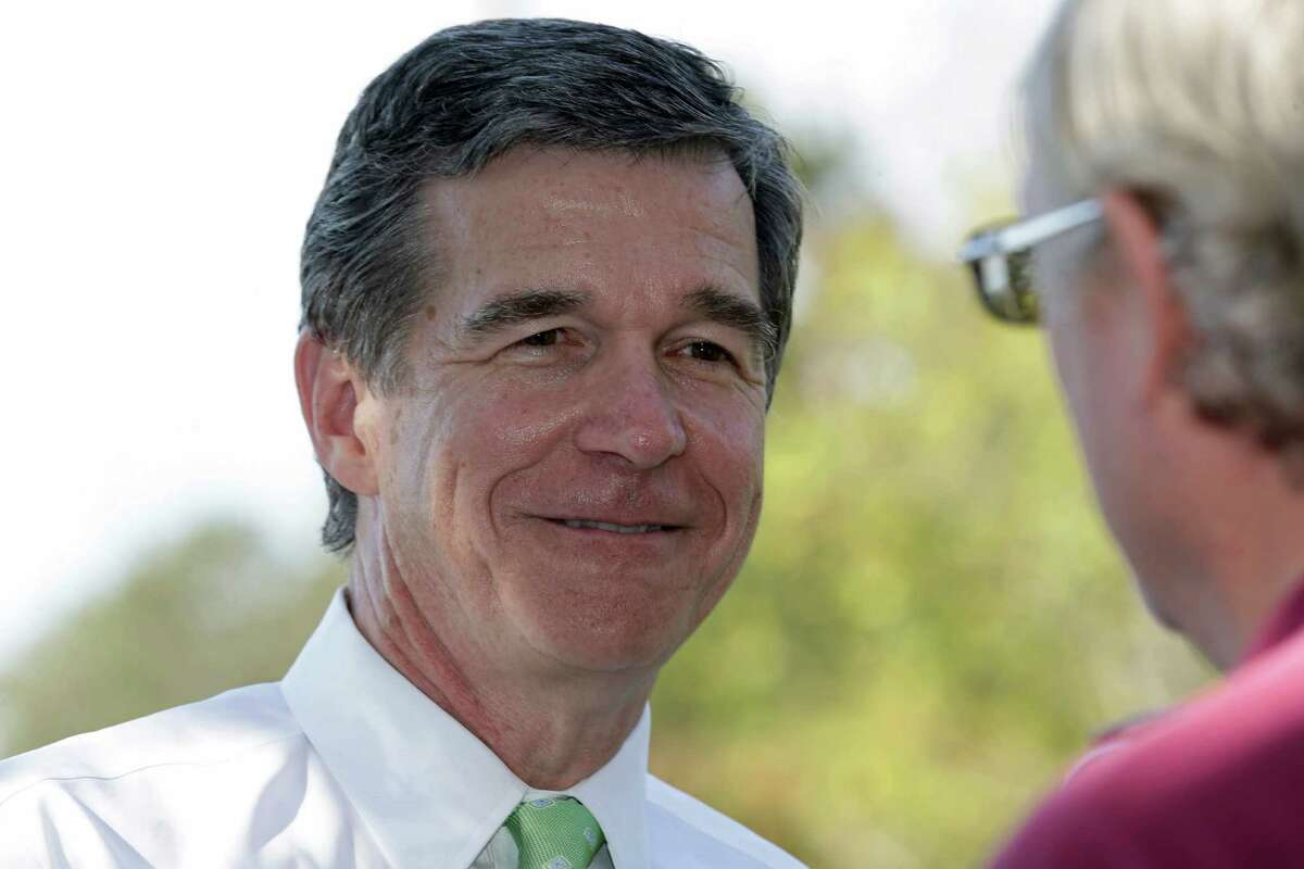 In this photo taken Thursday, Oct. 20, 2016 Democratic gubernatorial candidate Attorney General Roy Cooper mingles with voters at the polls during early voting in Raleigh, N.C. The North Carolina governor's race is everything voters anticipated it would be: expensive attack ads and barbed debates before what's essentially a referendum on the state's recent rightward tilt under Republican rule, particularly the state law limiting protections for LGBT people _ known as House Bill 2. (AP Photo/Gerry Broome)