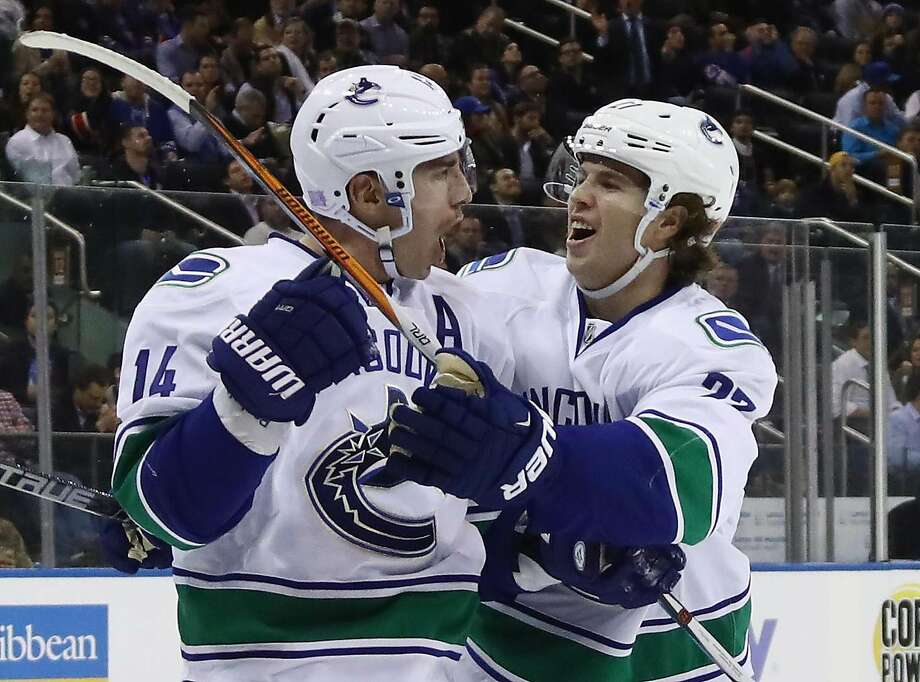 Vancouver's Alexandre Burrows (14 ) celebrates with Ben Hutton after scoring midway through the third period. Photo: Bruce Bennett, Getty Images