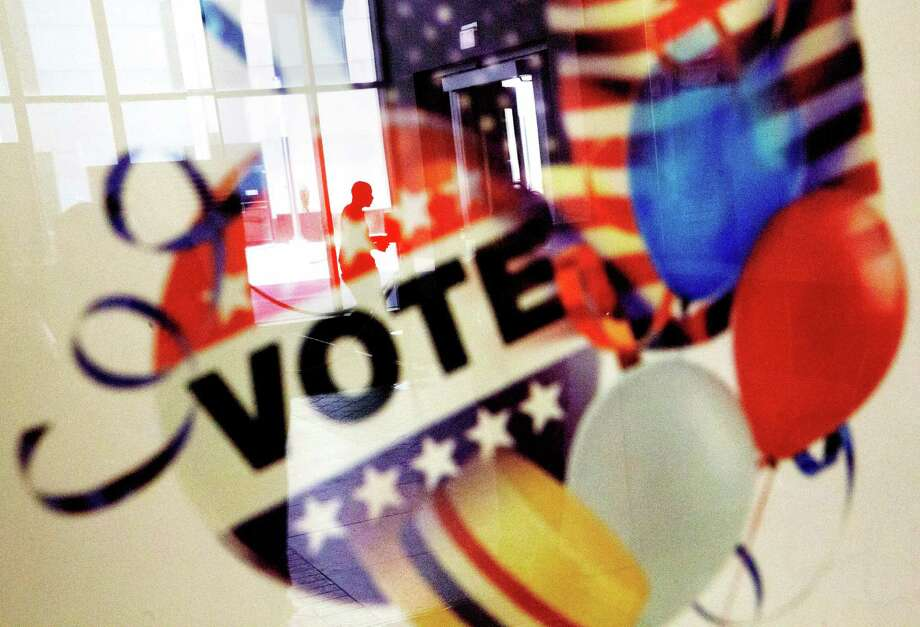 In this Nov. 1, 2016, photo, a voter is reflected in the glass frame of a poster while leaving a polling site in Atlanta, during early voting ahead of the Nov. 8 election day. Sen. Dawn Buckingham, R-Lakeway, will chair the Republican Party of Texas' Victory fund raising money to improve GOP voter registration and turnout for the 2018 election. (AP Photo/David Goldman) Photo: David Goldman, STF / Copyright 2016 The Associated Press. All rights reserved.