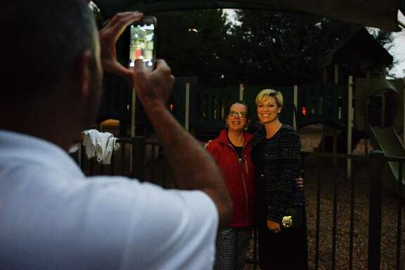 State Rep. Jim Murphy takes a photo Tuesday of State Rep. Sarah Davis, right, with supporter Lisa White Watkins outside the Colonial Park Recreation Room.