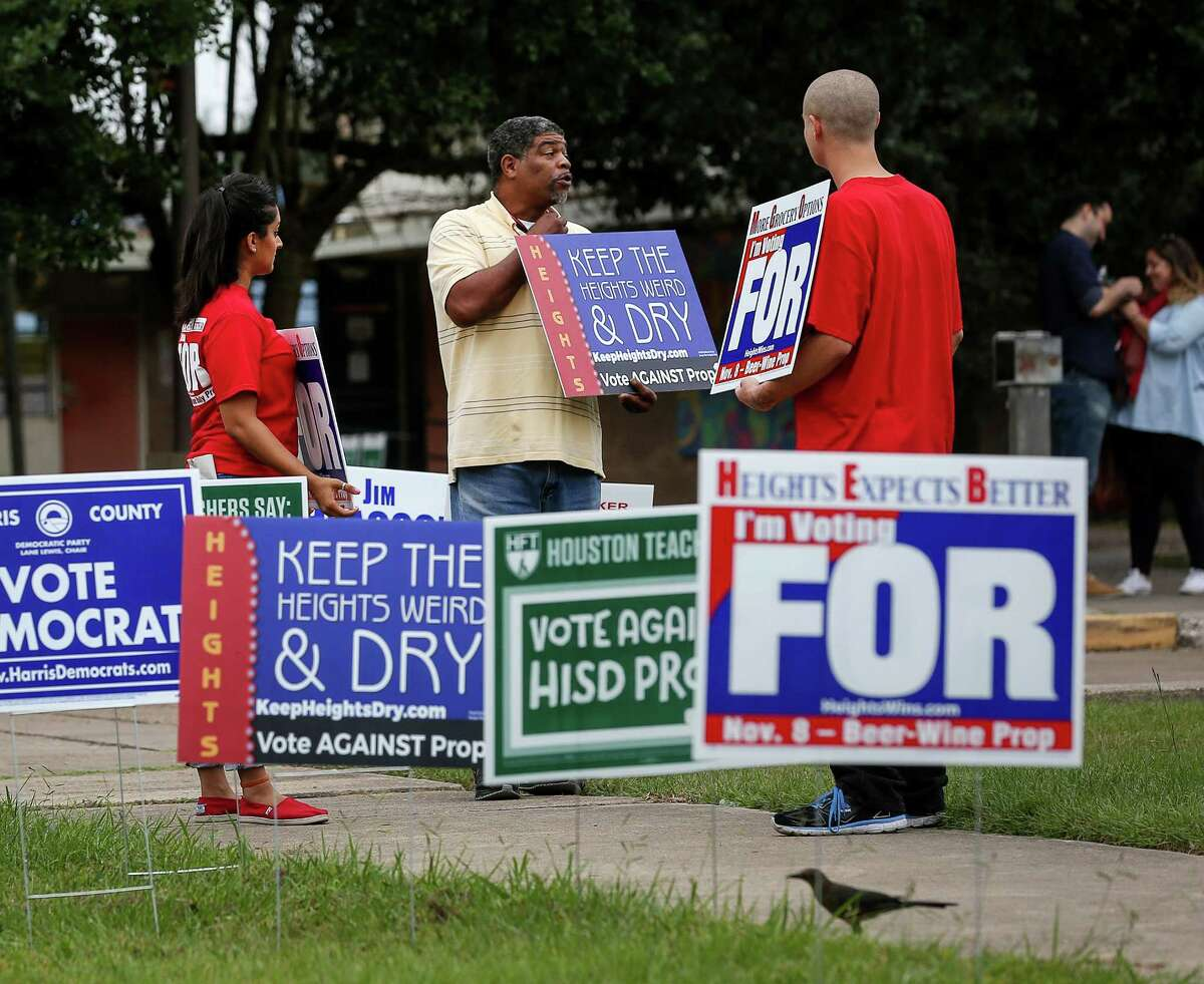 Kasey Barnett, center, talks with Puja Kapoor, an HEB employee, left, and Sebastian Small, both supporters of Prop. 1, at the Love Park Community Center in the Heights Tuesday.