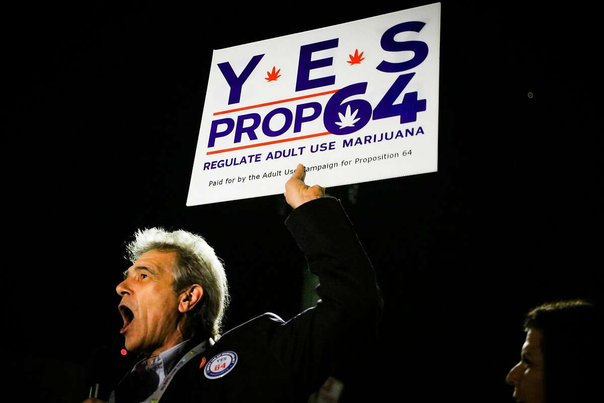 Chris Conrad holds up a Prop. 64 sign while speaking at a press conference to announce the passing of Prop. 64 outside the Berkeley Patients Group Party, at The New Parish Oakland, California, on Tuesday, Nov. 8, 2016.