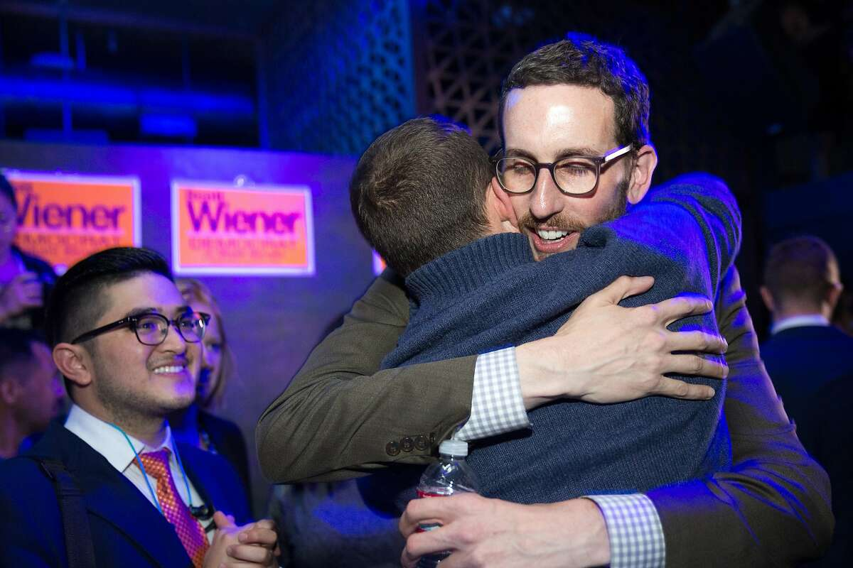 From right: Scott Wiener hugs his campaign manager, Jeff Sparks, as supporter and campaign volunteer Jason Galisatus cheers, during Wiener's election night party at Beaux, on Tuesday, Nov. 8, 2016 in San Francisco, Calif. Wiener is a state Senate candidate.