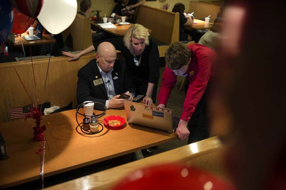 Rep. Gary Glenn, from left, his wife Annette Glenn and his campaign manager Jeremiah Ward look at polling information from Midland County at Pizza Sam's in Midland Tuesday evening. Glenn defeated Democratic challenger Geoff Malicoat. Photo: Brittney Lohmiller/Midland Daily News/Brittney Lohmiller