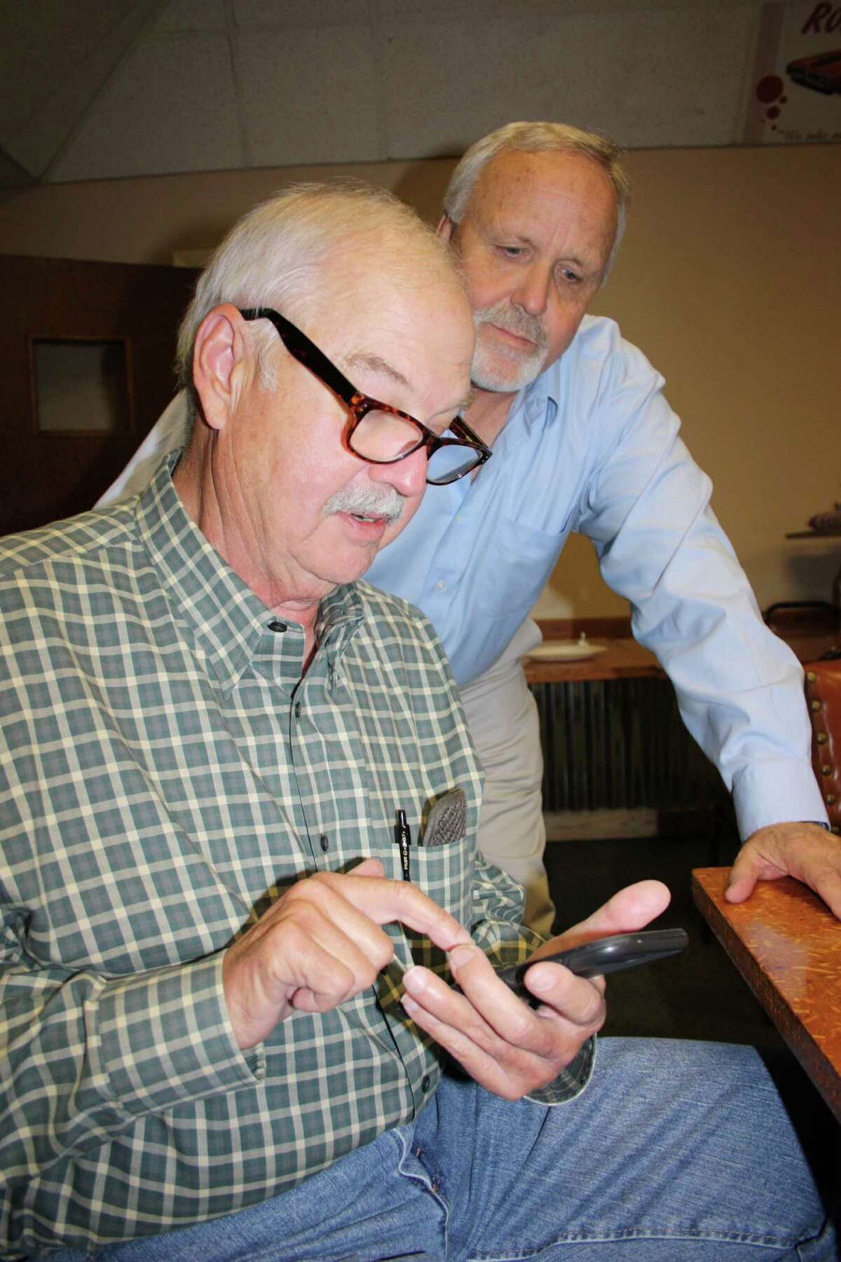 Liberty County Pct. 1 Commissioner Mike McCarty checks the latest election results on his phone while County Judge Jay Knight looks on. McCarty, a Republican, easily won reelection as he had no opposition in the Nov. 8 general election.