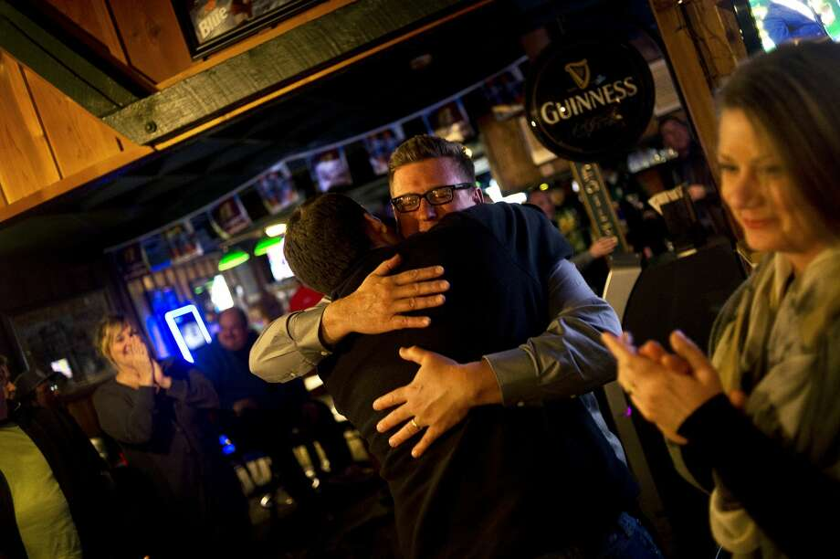 ERIN KIRKLAND | ekirkland@mdn.net Republican candidate for Michigan's 99th House District Roger Hauck hugs his son Matthew Hauck as wife Raschelle Hauck, right, looks on after Hauck learned of his victory at Green Spot Pub in Mt. Pleasant on early Wednesday morning. Photo: Erin Kirkland/Midland Daily News