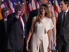 Republican presidential candidate Donald Trump, flanked by wife Melania, pumps his fist as he arrives with members of his family for an election night party at the New York Hilton Midtown in New York on November 9, 2016.  Trump won the US presidency. / AFP PHOTO / Timothy A. CLARYTIMOTHY A. CLARY/AFP/Getty Images