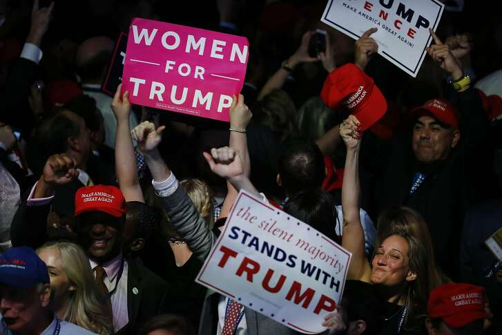 Attendees hold signs while cheering during an election night party at the Hilton Midtown hotel in New York, U.S., on Wednesday, Nov. 9, 2016. Trump was elected the 45th president of the United States in a repudiation of the political establishment that jolted financial markets and likely will reorder the nation's priorities and fundamentally alter America's relationship with the world. Photographer: Andrew Harrer/Bloomberg